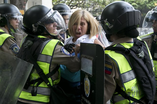 An anti-government demonstrator is pushed away by Bolivarian National Police who block protesters from reaching the headquarters of the national electoral body, CNE, in Caracas, Venezuela, Wednesday, May 18, 2016. (Photo by Ariana Cubillos/AP Photo)
