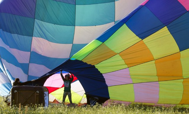 """A participant helps inflate a hot air balloon at the Cup Hot Air event during the Air Sports festival titled """"70 Years of Peaceful Sky"""" in Minsk, Belarus July 18, 2015. (Photo by Vasily Fedosenko/Reuters)"""