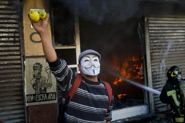 A man wearing a Guy Fawkes mask hawks lemons as a fireman works to put out a fire during an anti-government protest that turned violent, near a Congress where Chile's President Michelle Bachelet gives her annual address, in Valparaiso, Chile, Saturday, May 21, 2016. (Photo by Esteban Felix/AP Photo)