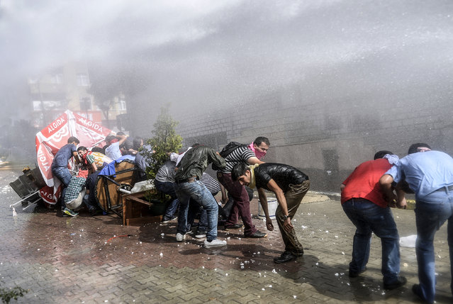 Left-wing militants protect themselves as Turkish anti-riot police fires water cannon to disperse a demonstration in Istanbul's Gazi district, on July 26, 2015. Tensions across the country are high, with police routinely using water cannon to disperse nightly protests in Istanbul and other cities denouncing IS and the government's policies on Syria. (Photo by Bulent Kilic/AFP Photo)