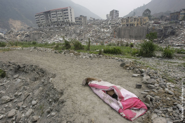 A covered body is laid in front of the ruins of a destroyed old city district, near a mountain at the earthquake-hit Beichuan county, Sichuan province, May 16, 2008