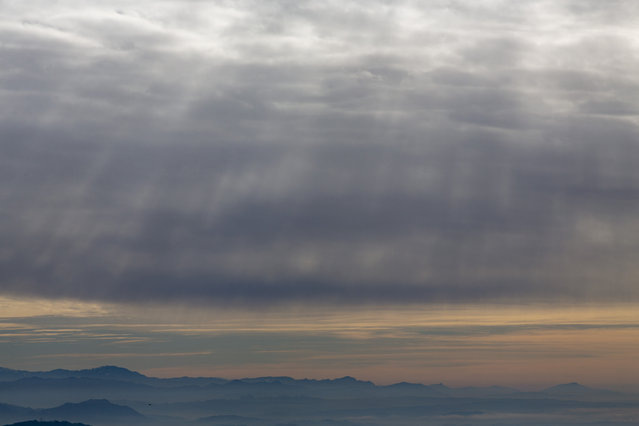 Sunlight filters in through a dense cover of clouds over the Kangra valley in Dharmsala, India, Wednesday, December 18, 2019. (Photo by Ashwini Bhatia/AP Photo)