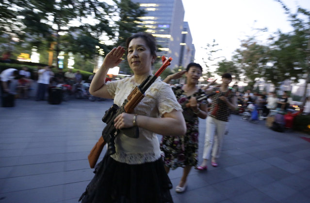 "Local women holding toy guns salute before they dance to revolutionary songs as part of their daily exercise at a square outside a shopping mall in Beijing, June 27, 2014. About 30 local residents formed this ""Nanguan"" art group that enjoys performing and dancing to revolutionary songs as part of their nightly fitness activity. (Photo by Jason Lee/Reuters)"