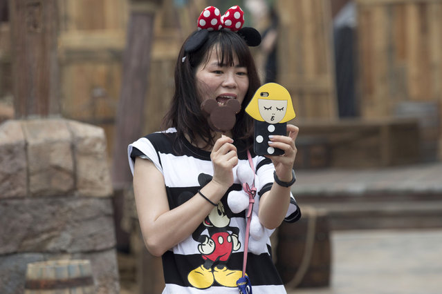 A visitor poses for a selfie with an ice cream shaped like the iconic Mickey Mouse character during a tour on the eve of the opening of the Disney Resort in Shanghai, China, Wednesday, June 15, 2016. (Photo by Ng Han Guan/AP Photo)