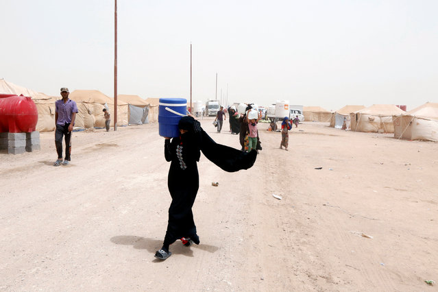 A woman, who fled from Falluja because of Islamic State violence, carries water at a refugee camp in Ameriyat Falluja, south of Falluja, Iraq, June 16, 2016. (Photo by Ahmed Saad/Reuters)