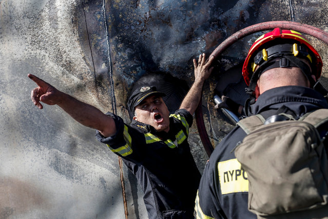 Firefighters try to extinguish a wildfire burning container boxes with telecommunication and radio equipment at the Radion Antenna Park atop of Ymmitos Mountain (Hymettus), after a wildfire that broke out at the foot of the mountain on the outskirt of Athens, Greece, 12 August 2019. A wildfire broke out in the forest of Paeania, suburb of Athens, was contained quickly by the fire brigade. (Photo by Kostas Tsironis/EPA/EFE)