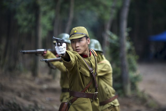 """An actor dressed as a historical Japanese army officer shoots a fake gun on the set of """"The Last Prince"""" television series at Hengdian World Studios in Hengdian July 23, 2015. There are eleven productions about the war against Japan being filmed at Hengdian World Studios. The facility itself, located in China's Zheijang province, is the biggest movie lot ever built. (Photo by Damir Sagolj/Reuters)"""
