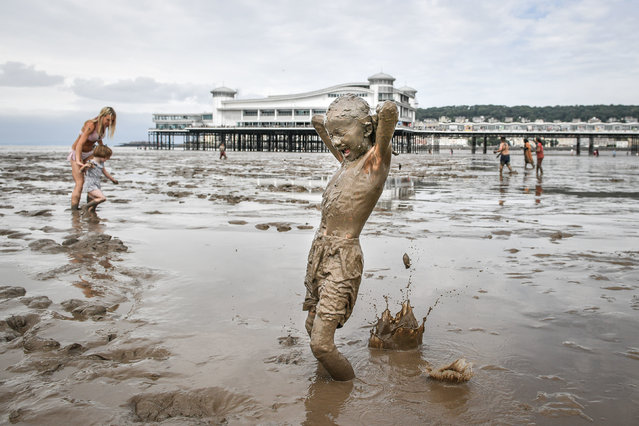 Blaze, 8, from Swindon, is covered from head to toe as he plays in the mud at Weston-super-Mare beach on August 4, 2019, as the tide recedes and the huge expanse of mud flats cover the beach where holidaymakers enjoy splashing around. (Photo by Ben Birchall/PA Images via Getty Images)