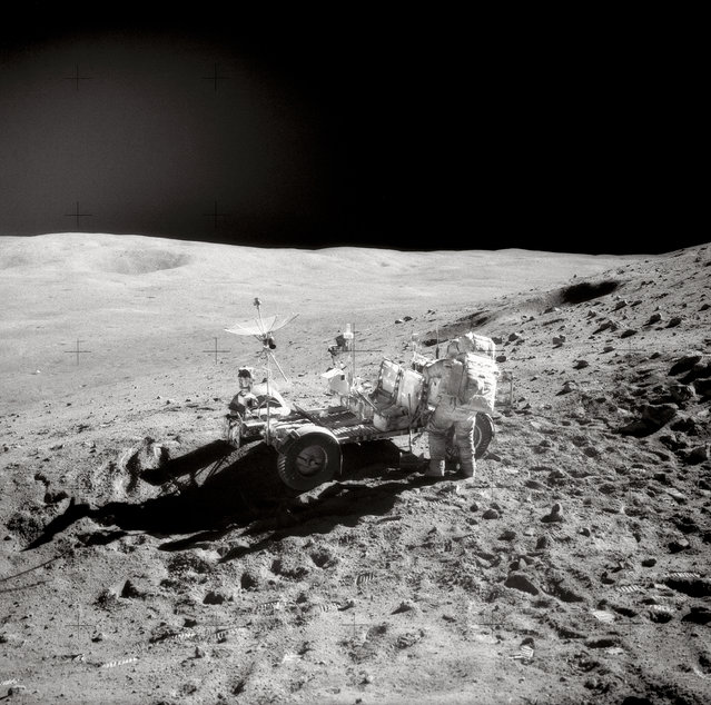 "Astronaut John W. Young, Commander of the Apollo 16 mission, replaces tools in the hand tool carrier at the aft end of the ""Rover"" Lunar Roving Vehicle (LRV) during the second Apollo 16 extravehicular activity (EVA-2) at the Descartes landing site. This photograph was taken by Astronaut Charles M. Duke Jr., Lunar Module pilot. Smokey Mountain, with the large Ravine crater on its flank, is in the left background. This view is looking Northeast. (Photo by NASA)"