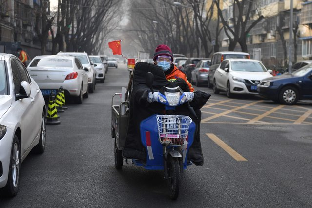 """A cleaner wears a mask and goggles as he commutes on a street in Beijing on February 11, 2020. The death toll from a new coronavirus outbreak surged past 1,000 on February 11 as the World Health Organization warned infected people who have not travelled to China could be the spark for a """"bigger fire"""". (Photo by Greg Baker/AFP Photo)"""