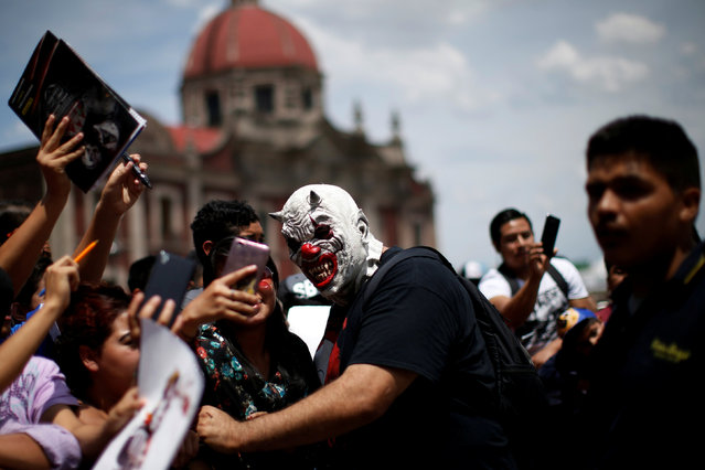 A Mexican wrestler known as Murder Clown sign autographs during the annual lucha libre pilgrimage to the Basilica of Our Lady Guadalupe in Mexico City, Mexico August 17, 2017. (Photo by Carlos Jasso/Reuters)