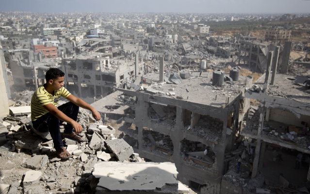 A Palestinian man looks out over destruction in part of Gaza City's al-Tufah neighbourhood as the fragile ceasefire in the Gaza Strip entered a second day on August 6, 2014 while Israeli and Palestinian delegations prepared for crunch talks in Cairo to try to extend the 72-hour truce. The ceasefire, which came into effect on August 5, has brought relief to both sides after one month of fighting killed 1,875 Palestinians and 67 people on the Israeli side. (Photo by Mahmud Hams/AFP Photo)