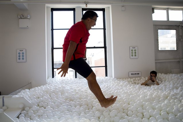 "A man leaps into the ""JumpIn!"" ball pit, an interactive art installation by creative agency Pearlfisher made up of 81,000 white balls, in New York City August 25, 2015. (Photo by Mike Segar/Reuters)"