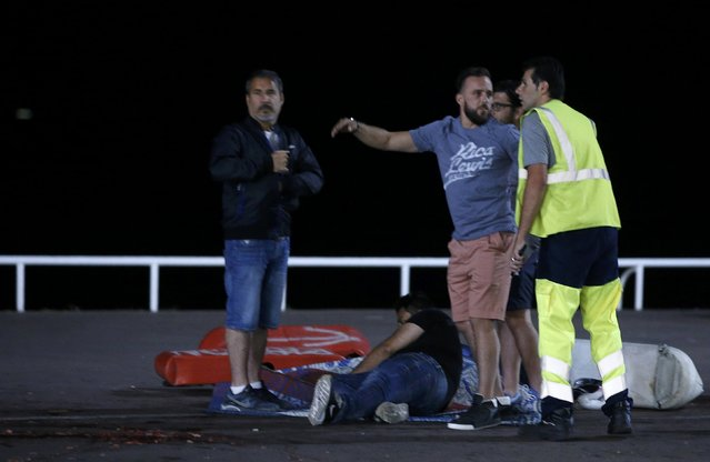 An injured individual is seen on the ground after at least 30 people were killed in Nice, France, when a truck ran into a crowd celebrating the Bastille Day national holiday July 14, 2016. (Photo by Eric Gaillard/Reuters)