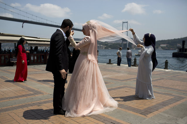 A new married couple poses for photos in front of the Bosporous bridge in central Istanbul, Sunday, July 17, 2016. Rather than toppling Turkey's strongman president, a failed military coup that left more than 250 dead appears to have bolstered Recep Tayyip Erdogan's immediate grip on power and boosted his popularity. (Photo by Petros Giannakouris/AP Photo)