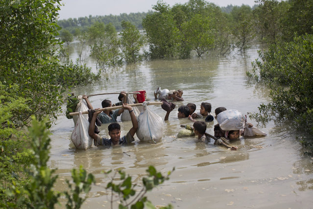 A Rohingya family reaches the Bangladesh border after crossing a creek of the Naf river on the border with Myanmmar, in Cox's Bazar's Teknaf area, Monday, September 4, 2017. (Photo by Bernat Armangue/AP Photo)