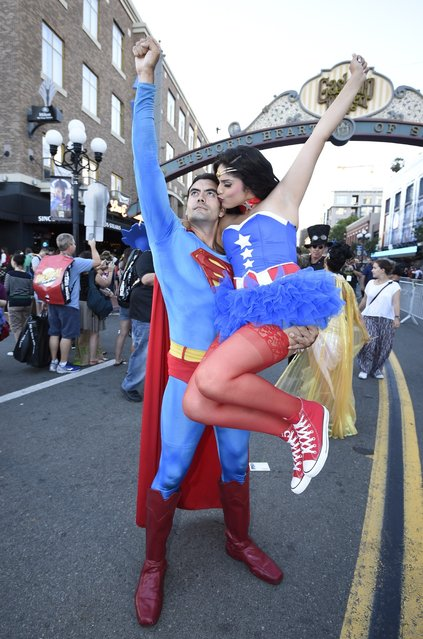 Sergio Valente, dressed as Superman, lifts Jessica Randall, dressed as Vixen, as she gives him a kiss outside of the convention center on day one of Comic-Con International held at the San Diego Convention Center Thursday, July 21, 2016 in San Diego. (Photo by Denis Poroy/Invision/AP Photo)