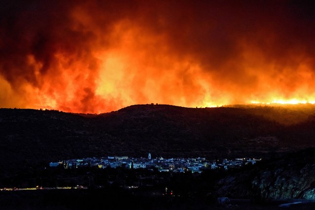 A picture made available on 26 July 2016 shows dense smoke over Lithi village during a wildfire on Chios island, Greece, 25 July 2016. The huge wildfire that broke out early 25 July 2016, on the island of Chios which has burned 3,500 hectares of forest and farm land, set under control. Over 90 percent of the mastic trees at the villages of Lithi, Elata and Vessa were destroyed while a large number of mastic trees were burned at the villages of Mesta, Armolia and Pyrgi. (Photo by Kostas Koyrgias/EPA)