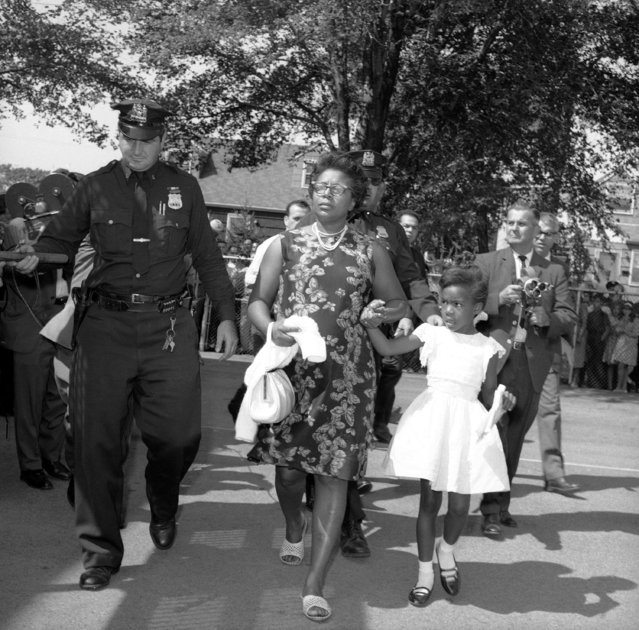 Eleanor Butler and her daughter Leonora, 6, are escorted by Lynbrook, Long Island, New York police at the Davison Avenue School in Lynbrook, New York, September 4, 1963 after her arrest. Police arrested five black parents and a Long Island civil rights official for loitering as they staged a sit-in at the predominantly white elementary school. (Photo by Jack Kanthal/AP Photo)