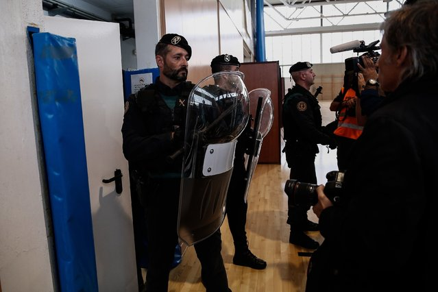 Police and gendarmerie crew intervene the voters in the Catalan independence referendum at a sport hall, where Catalan President Carles Puigdemont would be voting, in Girona, Spain on October 1, 2017. Tensions rose in some voting centers, including Saint Julia de Ramis School in Girona and Ramon Llull School in Barcelona, as dozens of anti-riot Spanish police blocked Catalan activists from voting. (Photo by Burak Akbulut/Anadolu Agency/Getty Images)