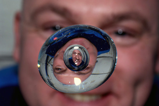 Astronaut Andre Kuipers watches a bubble in a drop of water as he enjoys his last days of weightlessness aboard the International Space Station, on June 24, 2012. (Photo by AP Photo/NASA, Andre Kuipers)