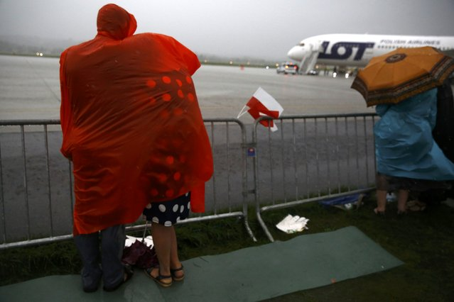 People during heavy rain under raincover wait for Pope Francis farewell ceremony at Balice airport near Krakow, Poland July 31, 2016. (Photo by Kacper Pempel/Reuters)
