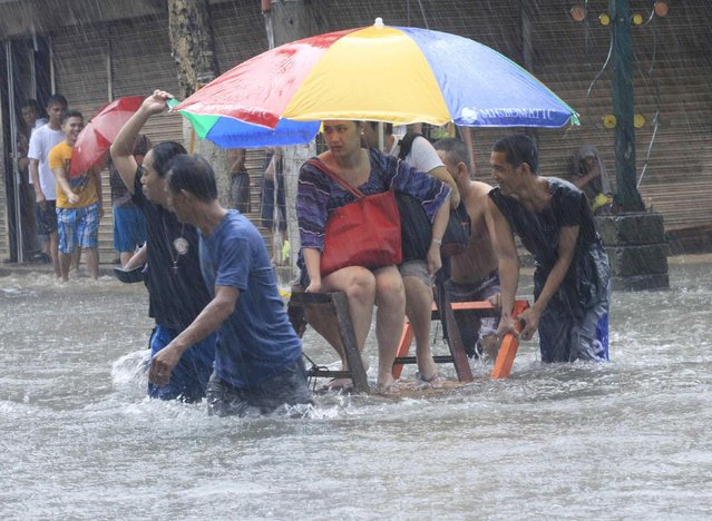 Stranded passengers ride on a improvised pushcart to cross a flooded street after tropical storm Fung-Wong battered metro Manila September 19, 2014. (Photo by Erik De Castro/Reuters)