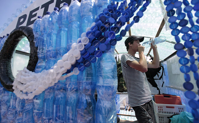 Jan Kara drinks water from a plastic bottle on his boat, made with plastic bottles, on the Elbe river near Kostelec nad Labem July 15, 2014. (Photo by David W. Cerny/Reuters)