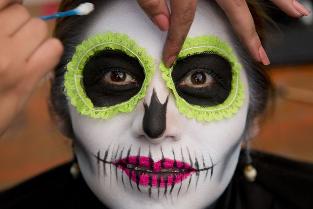A woman has her make up applied as she waits for the start of a Day of the Dead parade to begin along Mexico City's main Reforma Avenue, Saturday, October 28, 2017. (Photo by Eduardo Verdugo/AP Photo)