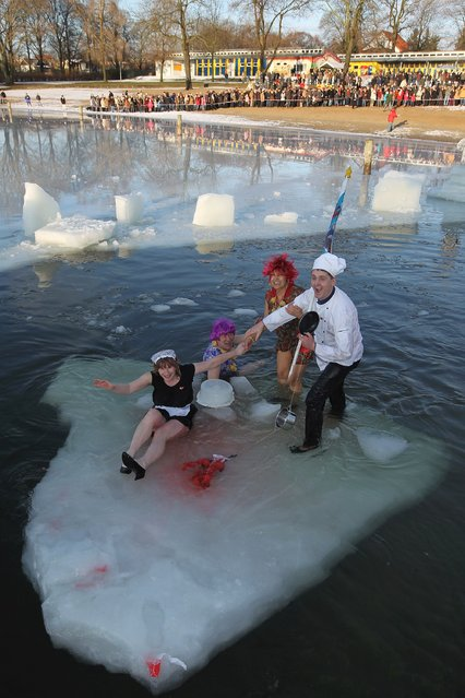 """Ice swimming enthusiasts take to the frigid waters of Orankesee lake during the 27th annual """"Winter Swimming in Berlin"""", which this year had a kitchen theme for dress, on January 8, 2011 in Berlin, Germany. (Photo by Sean Gallup)"""