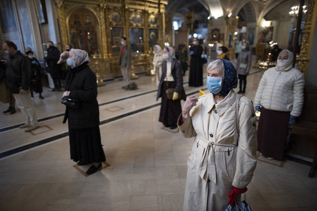 Parishioners wearing face masks to protect against coronavirus, observe social distancing guidelines cross themselves as they attend service at the Epiphany Cathedral in Moscow, Russia, Tuesday, June 2, 2020. Churches in Moscow reopen to believers after a two-month lockdown imposed to control the spread of the coronavirus. (Photo by Alexander Zemlianichenko/AP Photo)