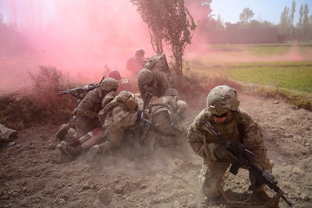 U.S. Army soldiers protect a wounded comrade from dust and smoke flares after an improvised explosive device blast during a patrol near Baraki Barak base in Logar Province, Afghanistan, on October 13, 2012. The soldier, 21-year-old Pvt. Ryan Thomas from Oklahoma, suffered soft tissue damage and after surgery in Afghanistan was scheduled to be evacuated to Germany. (Photo by Munir Uz Zaman/AFP)