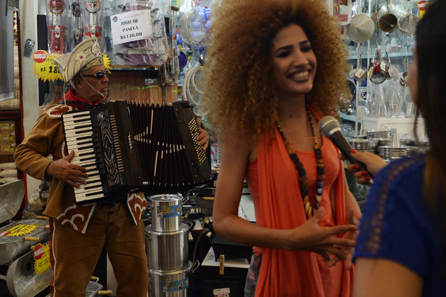 José Pereira de Souza plays an accordion as actress and model Tatiana Melo gives a television interview in Feira Nordestina outside of the Olympic periphery on Wednesday, August 17, 2016. (Photo by Aaron Ontiveroz/The Denver Post)