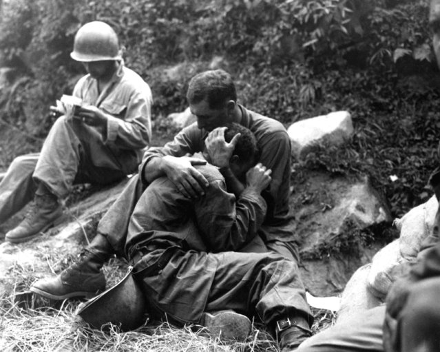 A grief stricken American infantryman whose buddy has been killed in action is comforted by another soldier. In the background a corpsman methodically fills out casualty tags, Haktong-ni area, Korea. August 28, 1950. (Photo by Sfc. Al Chang)