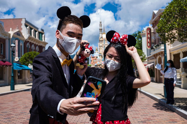 Visitors dressed in costumes take a selfie at Hong Kong's Disneyland on June 18, 2020, after the theme park officially reopened following nearly five months of closure in a fresh boost for a city that has largely managed to defeat the COVID-19 coronavirus. (Photo by Anthony Wallace/AFP Photo)