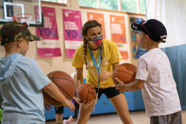 A counselor wearing a protective face mask plays with children as summer camps reopen amid the spread of coronavirus at Carls Family YMCA summer camp in Milford, Michigan, June 23, 2020. (Photo by Emily Elconin/Reuters)