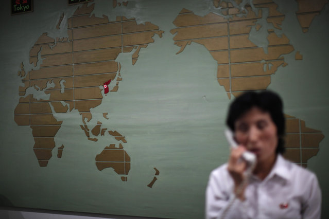 A world map, with the Korea peninsula marked in red, is seen as a hotel receptionist talks on the phone in Rason city, northeast of Pyongyang, August 29, 2011. (Photo by Carlos Barria/Reuters)