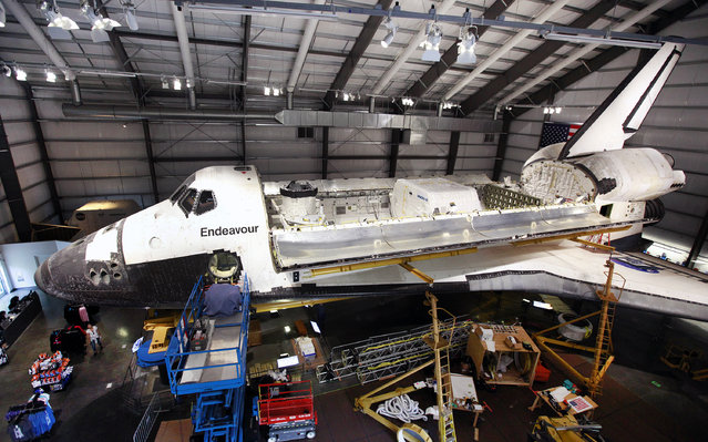 The payload bay doors of the space shuttle Endeavour, housed at the California Science Center, stand open after the installation of a space lab and storage pod on Friday, October 10, 2014 in Los Angeles. The equipment being installed was flown on some missions. A crew on Thursday delicately positioned the 3,000-pound (1,360-kilogram) portable lab and pod inside the orbiter's huge cargo bay. Workers also installed a replica robotic arm, airlock and docking system. (Photo by Richard Vogel/AP Photo)