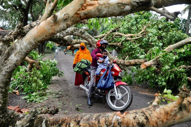 A man with a child ride on motorbike in the street blocked by trees that were uprooted by Cyclone Amphan in Satkhira, Bangladesh on May 21, 2020. (Photo by Km Asad/Reuters)