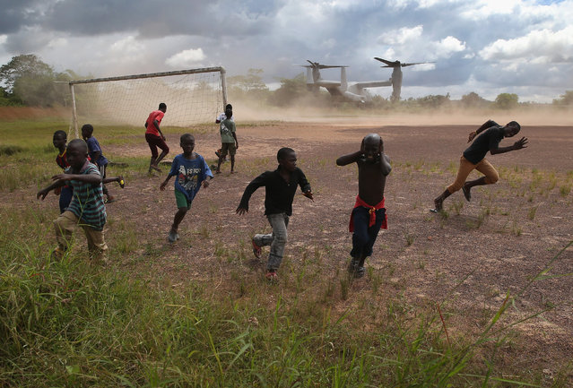 Boys run from the blowing dust as a U.S. Marine MV-22 Osprey tiltrotor departs the site of an Ebola treatment center under construction on October 15, 2014 in Tubmanburg, Liberia. The center is the first of 17 Ebola treatment centers being built by Liberian forces under American supervision as part of Operation United Assistance to combat the Ebola epidemic. (Photo by John Moore/Getty Images)