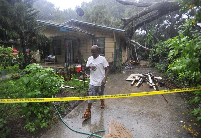 """Andre Anton stops from gathering his families belongings as the rain continues pour inside of his home after a large tree crashed through the roof Wednesday, August 31, 2016, in Tampa, Fla. """"We have no place to go right now, trying to figure it out"""", said Dorman. The National Hurricane Center in Miami says Tropical Storm Hermine is gaining strength as it rumbles toward Florida's Gulf Coast. (Photo by Octavio Jones/Tampa Bay Times via AP Photo)"""