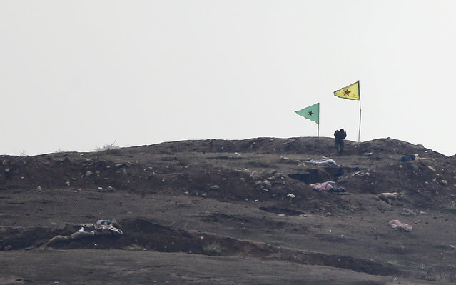 An armed man, presumed by local sources to be People's Protection Unit (YPG) fighters, stand near Kurdish flags at a checkpoint in the west of Syrian town of Kobani, October 17, 2014. (Photo by Kai Pfaffenbach/Reuters)