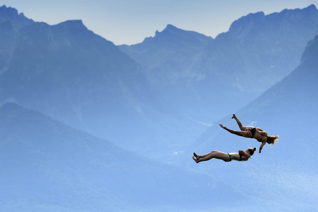 Two women jump into the Geneva Lake after having slipped on a water slide in front of the Swiss and French Alps mountains as they enjoy the sunny and warm weather during the Summerslide Festival in Clarens near Montreux, Switzerland, 03 September 2016. (Photo by Laurent Gillieron/EPA)