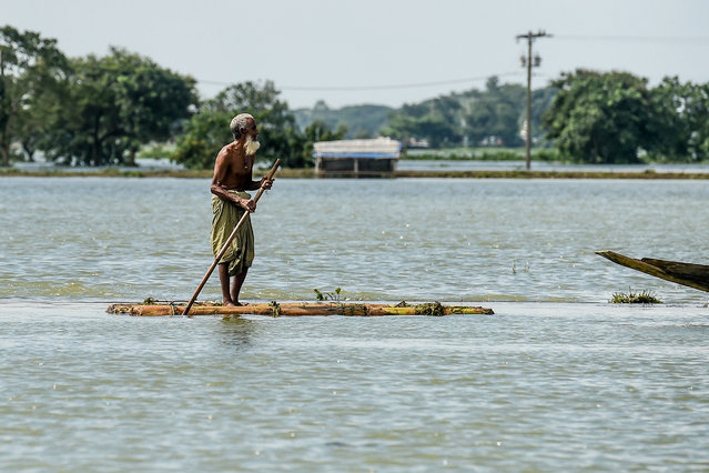 A man rides a makeshift raft in floodwaters in Sunamganj on July 16, 2020. (Photo by Munir Uz Zaman/AFP Photo)