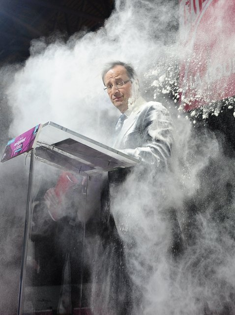 "In this February 1, 2012 file photo, an unidentified woman throws flour on French Socialist Party candidate for the 2012 presidential elections, Francois Hollande, in Paris. The woman ran to the side of the podium where Hollande stood to sign a ""social contract"" in favor of housing for all. (Photo by AP Photo/SZG)"