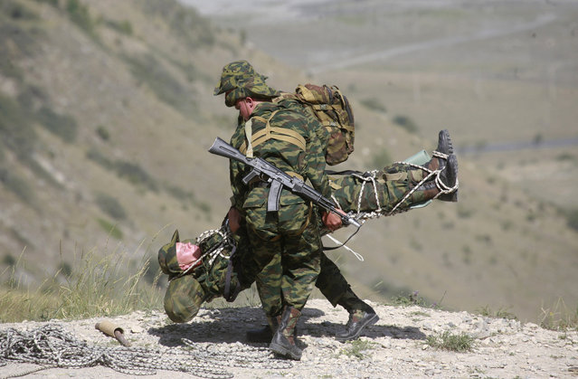 Russian soldiers from 34th motorized infantry mountain brigade, 58th Army, prepare to evacuate a fellow soldier acting as an injured person during a drill at the Darial range outside Russia's city of Vladikavkaz, July 28, 2010. (Photo by Kazbek Basayev/Reuters)