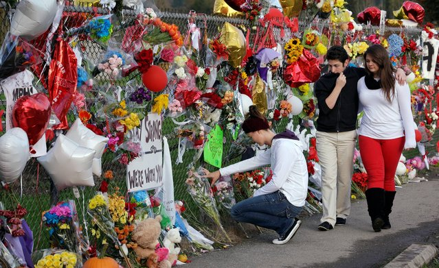 Dana Pattie, left, kneels at a block-long fence at Marysville-Pilchuck High School memorializing a shooting there last week as a couple walks past, Wednesday, October 29, 2014, in Marysville, Wash. A teacher who tried to intervene to stop the school shooting there last week says she reacted just as any of her colleagues would have. (Photo by Elaine Thompson/AP Photo)