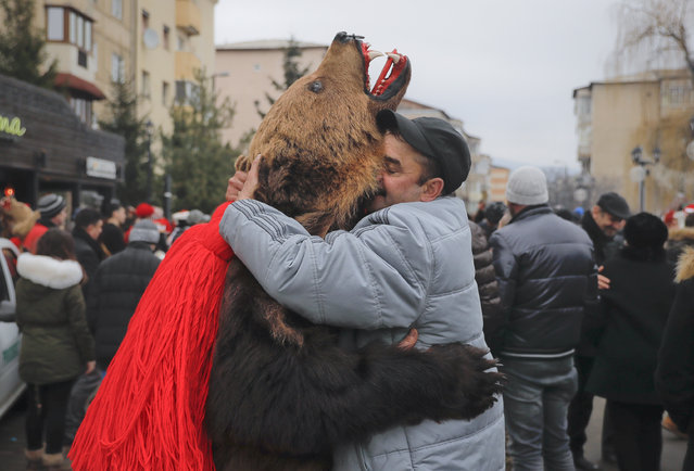 In this Saturday, December 30, 2017, picture men, one wearing a bear fur costume, hug during an annual bear parade in Comanesti, Romania. (Photo by Vadim Ghirda/AP Photo)