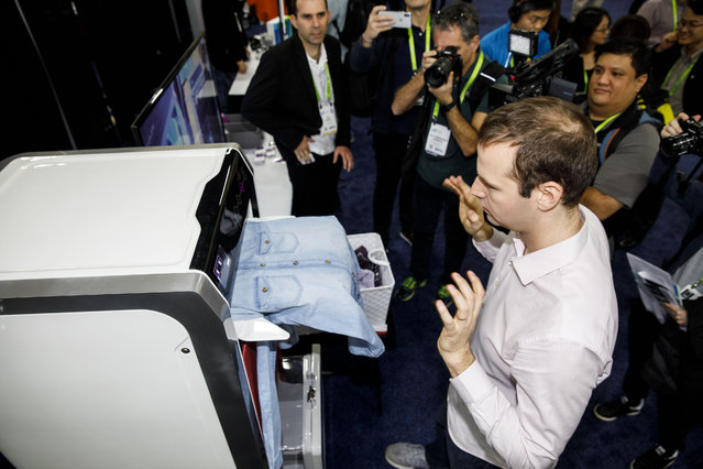 An attendee tries a FoldiMate Inc. robotic laundry folding machine during the CES Unveiled event at the 2018 Consumer Electronics Show (CES) in Las Vegas, Nevada, U.S., on Sunday, January 7, 2018. (Photo by Patrick T. Fallon/Bloomberg)