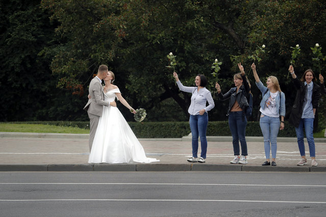 A newly wed couple kiss as Belarusian opposition supporters hold flowers during a protest in Minsk, Belarus, Thursday, August 20, 2020. Demonstrators are taking to the streets of the Belarusian capital and other cities, keeping up their push for the resignation of the nation's authoritarian leader. President Alexander Lukashenko has extended his 26-year rule in a vote the opposition saw as rigged. (Photo by Dmitri Lovetsky/AP Photo)